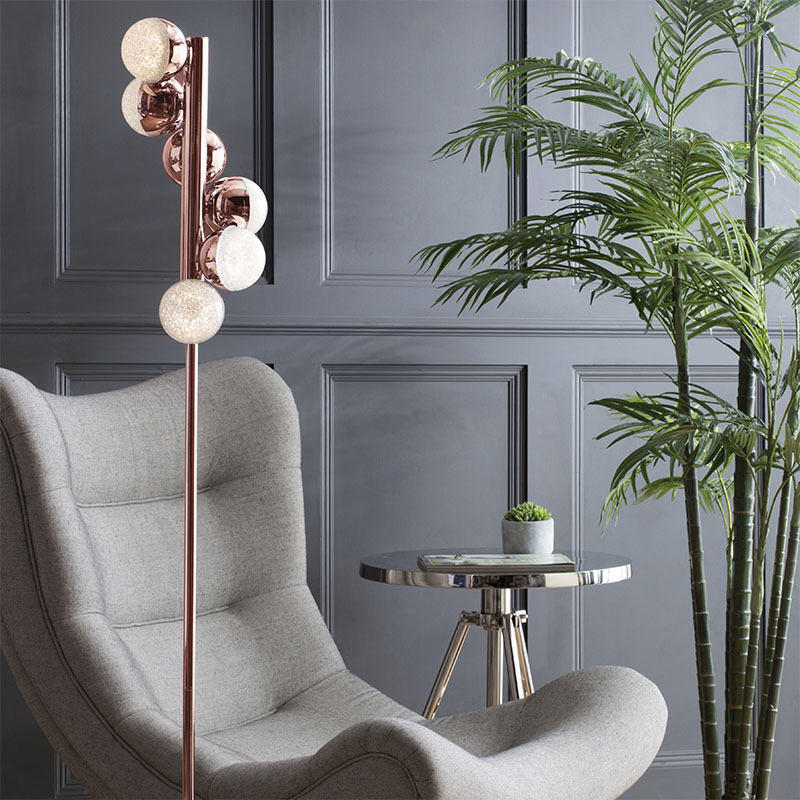 Visconte Corona Floor Lamp beside lounge chair in grey room with side table